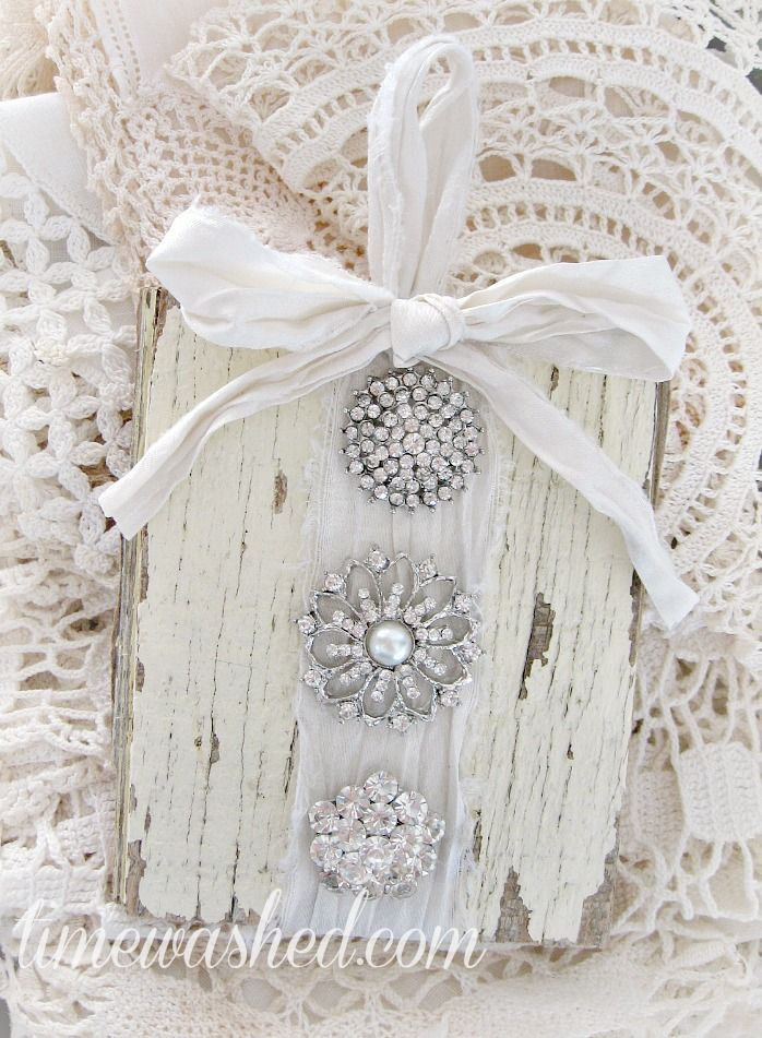 TIMEWASHED- what a great idea to do with old broaches in the same color on wood painted off white then stressed.  Love this idea!