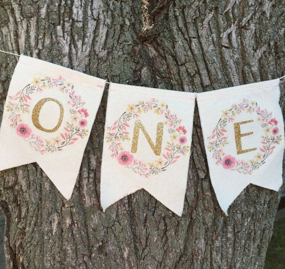 This is an adorable fabric ONE banner. The ONE is in bright gold glitter with the letters surrounded by a floral wreath. Perfect for a first