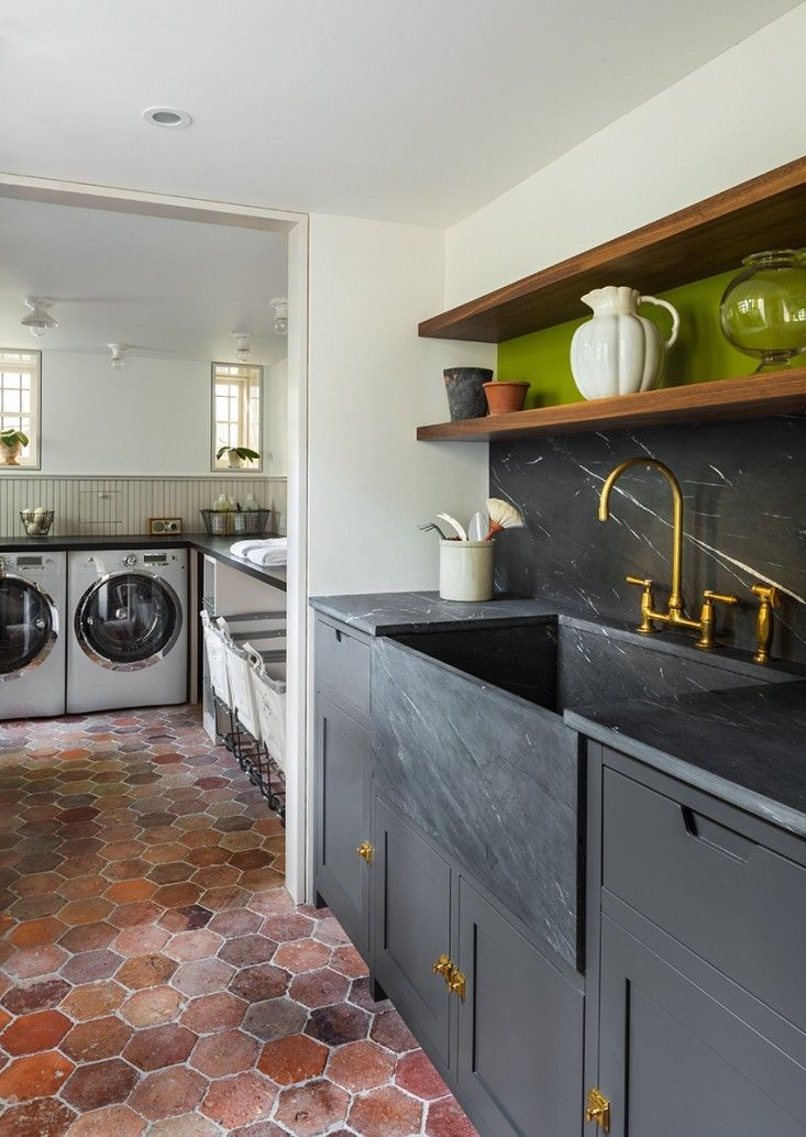 The utility room sink is made of marine black phyllite, which is similar in appearance to soapstone. The custom wood cabinets are painted in Kendall Charcoal by Benjamin Moore, and the flooring is French terracotta tile by Ann Sacks in Antique Dark.