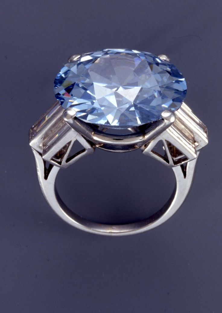 Given to the British Museum by an anonymous donor, the centerpiece of this ring is a brilliant-cut blue diamond weighing nearly 16 carats. The stone itself shows signs of being cut in the 1920s, however, the setting--a mount of platinum with three-stone baguette diamond shoulders suggests the style of the 1940s-1960s.