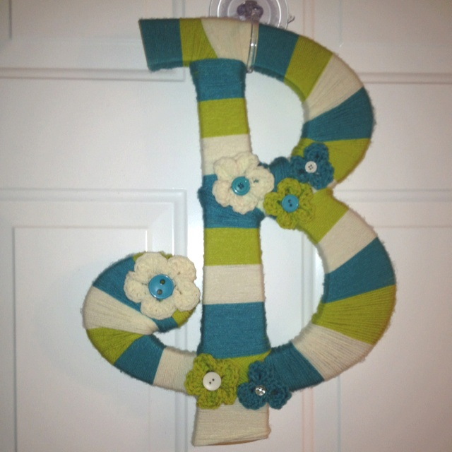 Wooden letter wrapped with yarn. Crocheted flowers.