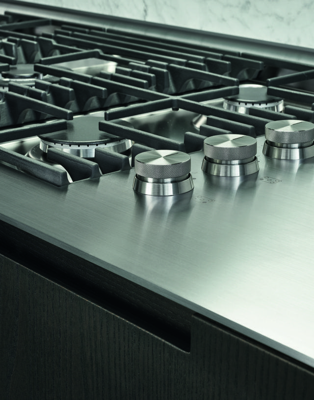 """Varenna_PHOENIX_ A detail of the worktop in steel scotch brite thickness 1/4"""", with personalised soldered hob with five burners Varenna by Scholtès."""