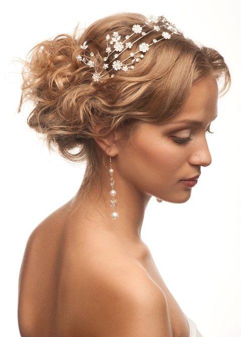 Für diese märchenhafte Frisur werden die Haare in eine voluminöse Lockenmähne verwandelt und anschließend locker am Hinterkopf aufgesteckt. Ein filigraner Haarreif mit Blüten macht den Look perfekt.
