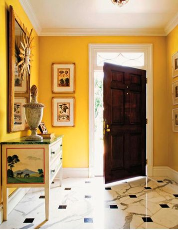 """Entrance with walls painted in bright yellow using """"Showtime by Benjamin Moore""""."""