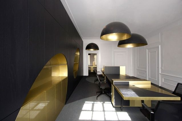 "Herengracht office. ""Golden and silver ovals shatter through the spaces like golden coins,"" say the designers. Large round lampshades, spray-painted gold on the inside, seem to cast light and shadow oval marks throughout the whole space."