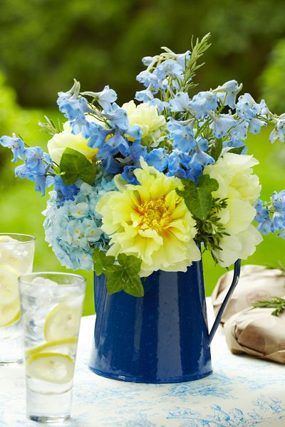 A simple Centerpiece for the table .... Blue enamel pitcher used instead...Such sweet centerpieces for an outdoor wedding or on your camping table- Delphinium, peonies, ivy, and rosemary, or any bunch of wild flowers.