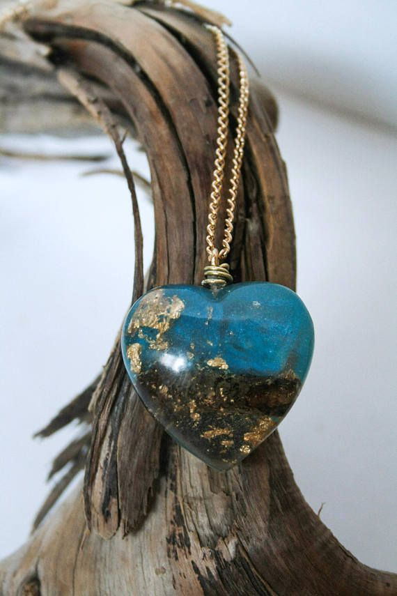 Heart pendant made of resin tinted with blue pearlex powder in a swirling pattern, and encasing a piece of moss-covered endangered oak branch (its habitat is largely restricted to Vancouver Island) and gold leaf. All pieces are made one at a time and entirely by hand, embedded with