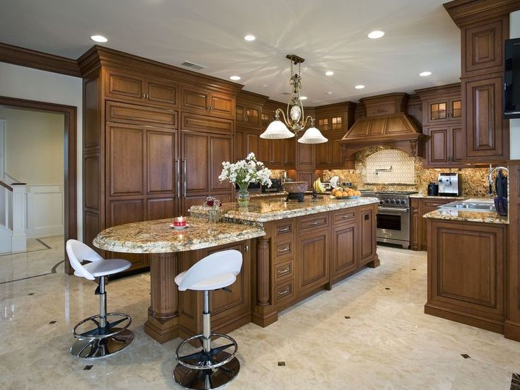 A Bi Level Island And Marble Countertops And Backsplash