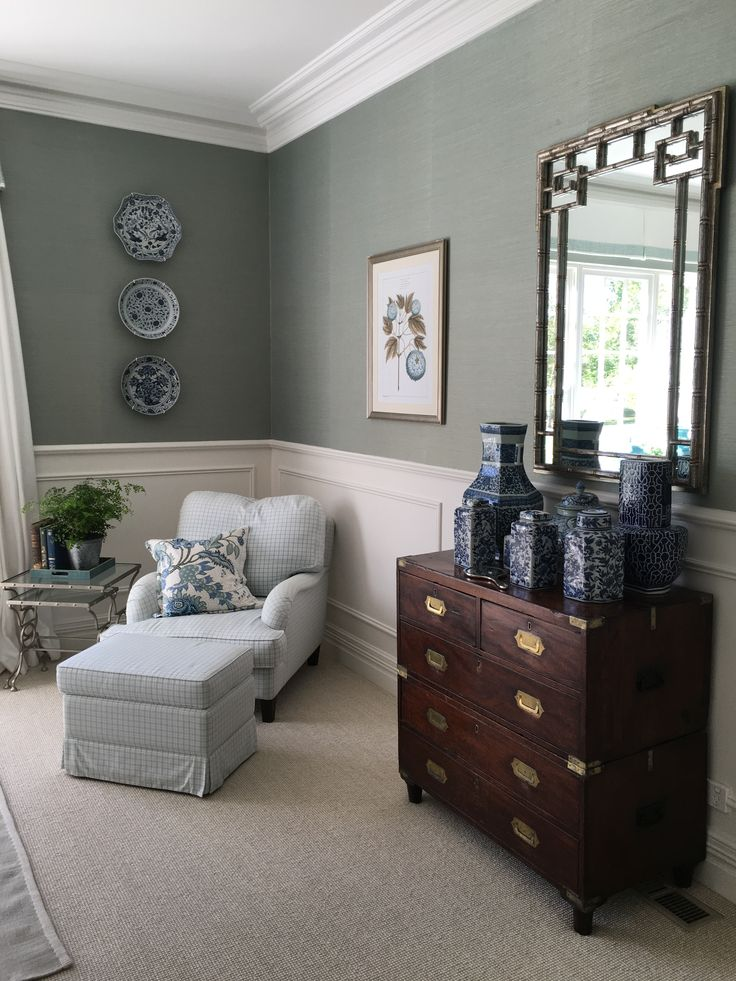 Schumacher duck egg blue grasscloth wallpaper, Jane Churchill check fabric chair/ottoman, antique campaign chest, vintage chinoiserie mirror, blue and white china collection by Melinda Hartwright Interiors