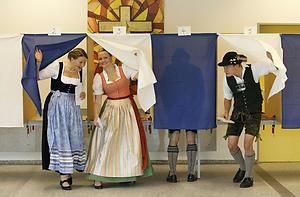 Voters wearing traditional Bavarian dress cast their ballots in German general election at polling station in Gaissach
