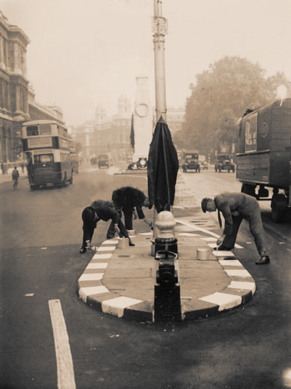 20th August 1939: Workmen paint white lines on a street island in Whitehall, London in preparation for a blackout in case of war