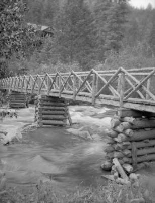 A wooden bridge spans the North Fork of the S. Platte River in Ferndale, Colorado. It was built by the owners of the cabin on the hill in the background, W. F. and Mary Byers Robinson.  From the Denver Library Western History Collection
