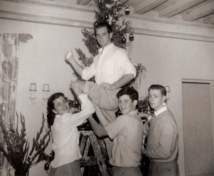 1948 family photo. At the Kennedy home in Palm Beach, Florida - Pat, Ted, and cousin Joe Gargan decorate the family Christmas tree and show off Bobby's knee for the camera.