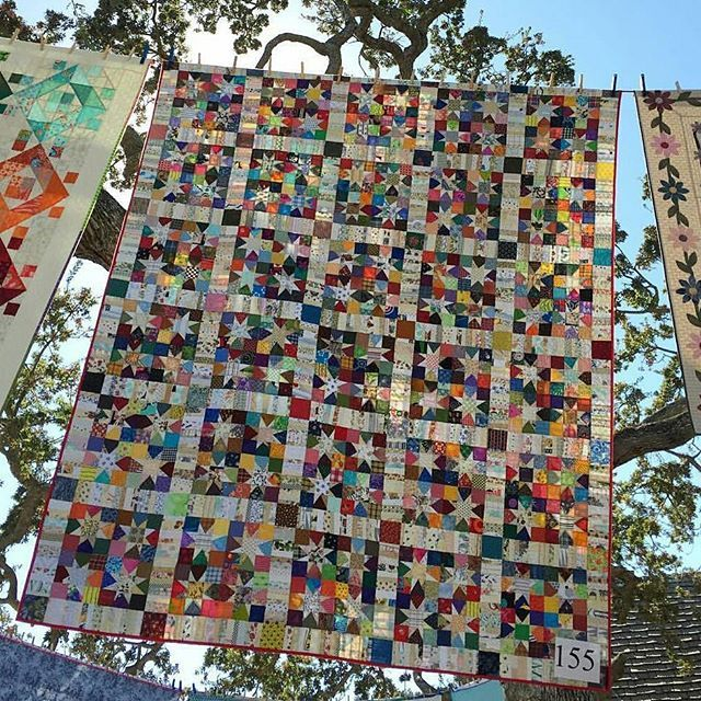 Another view/angle of my quilt Wonky Wishes hanging at Quilts in the Garden this past weekend!  Love the sky, the sun and the beautifully gnarly branches of the old oak behind.  Thank you for posting @jennifersampou! . . The pattern for Wonky Wishes is available in the Quiltville Store. Http://quiltville.com. . . #quilt #quilting #patchwork #quiltville #bonniekhunter #scrapquilt #sewallthescraps #sewmanyscraps #quiltshow #quiltsinthegarden