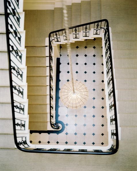 A staircase with a carpeted runner and black railings.