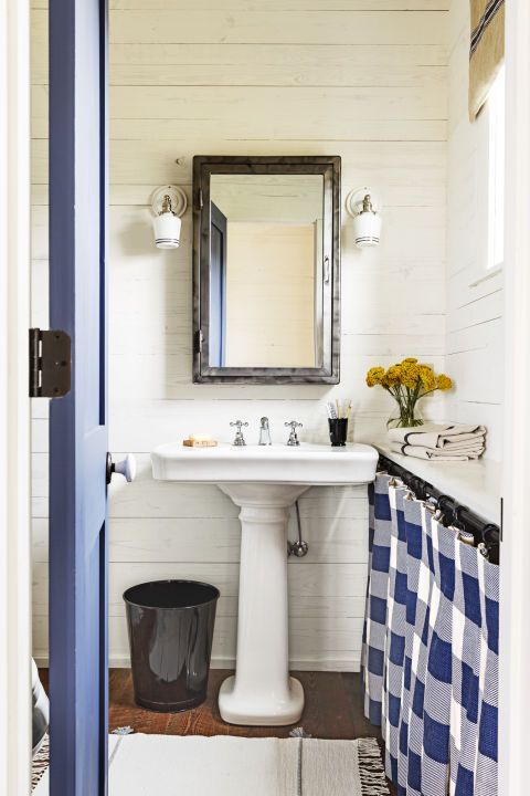 A plaid skirt hides bathroom storage. The walls of this room are covered in shiplap.