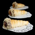 A photo of three Cannoncini di Sfoglia con Crema Pasticcera al Cioccolato (Pastry Horns filled with Chocolate Pastry Cream) place on white doilies and displayed in a row, one behind the other.