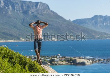 http://www.shutterstock.com/pic-227104516/stock-photo-african-black-man-standing-on-a-high-rock-overlooking-cape-town-as-he-points-and-scouts-the-blue.html?src=WuffEuvvGWj02MQSGcnIHQ-1-4 African Black Man, Standing On A High Rock Overlooking Cape Town As He Points And Scouts The Blue Sky, Ocean And Mountains On A Sunny Summers Day Stock Photo 227104516 : Shutterstock