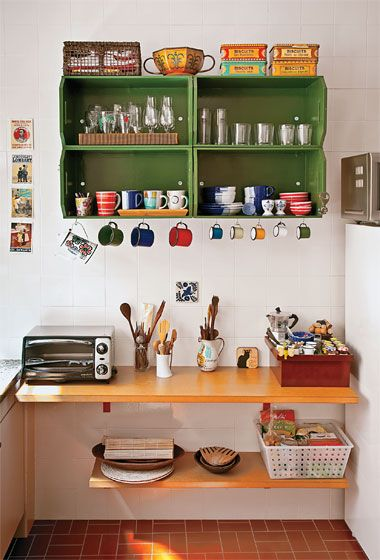 """Delicadas latas de biscoitos e bandejas colecionadas durante os tempos de garçonete na Europa se somam a ideias inspiradas de Ana Flávia: os ganchinhos na base do armário ordenam as canecas esmaltadas, que trazem cor ao espaço. Caixotes de frutas pintados com tinta esmalte (Capim Limão, da Suvinil) criam um armário. """"Basta lixar, pintar e parafusar"""", ensina a moça. Se quiser repetir a solução, uma possibilidade é recorrer ao site Madeira Usada."""
