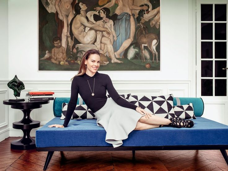 Actress Hilary Swank reclines on a daybed upholstered in velvet and leather by Dedar Milano and designed by Axel Huynh for Henryot & Cie. The side table is by India Madhavi, and the malachite stone sculpture is by Objet de Curiosité. Shoes, top, and skirt by Azzedine Alaia.