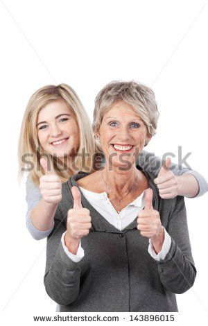 Portrait of grandmother and granddaughter showing thumbs up against white background