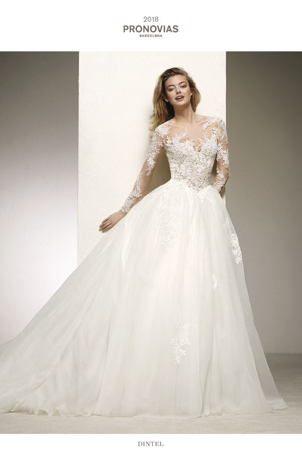 Sexy and elegant wedding dress that accentuates femininity through the tulle and volume of the ballgown skirt, combining it with a marvellous illusion bodice with matching sleeves, where the tattoo effect created by the crystal tulle, lace and floral thread embroidery envelop and embrace the bust and back.