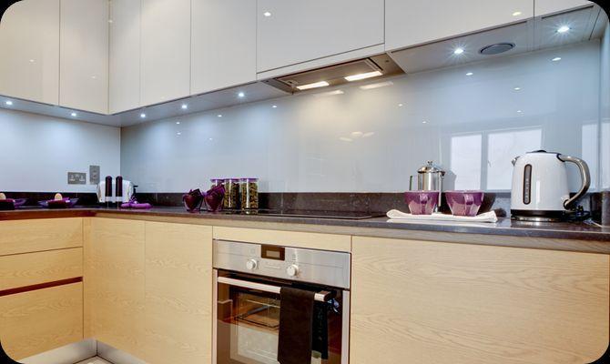blauwe glaswand in greeploze, houten keuken