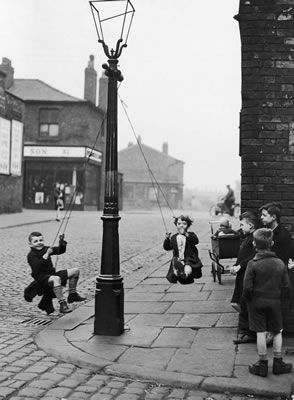 Children in a Manchester Street find their own enjoyment with the aid of a rope and a lamp post. Children playing in the street, swinging from a streetlight in March 1943. #Vintage #Classic #Old #Retro #Historic #OldFashioned #Manchester #MCR #NorthWest #photos #photographs #pictures #images #prints