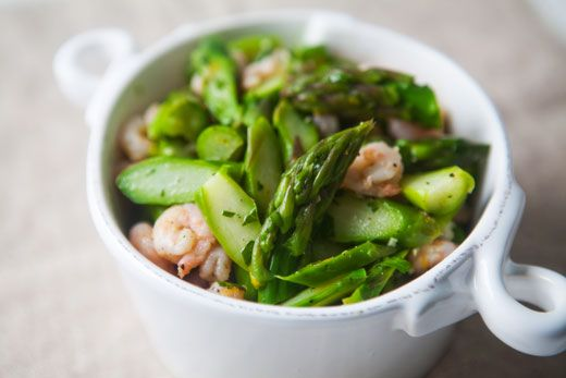 A simple asparagus salad with thinly sliced asparagus, shrimp, garlic, parsley, and dressed with olive oil and lemon juice.