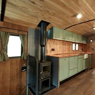 There is a wood burning stove and kitchen area wit…
