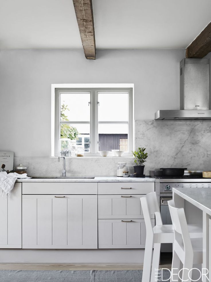 The kitchen's range, hood, and sink are all by Smeg, the fittings are by Vola, the counters are Carrara marble, and the cabinetry is painted in Farrow & Ball's Cornforth White. www.waringsathome.co.uk