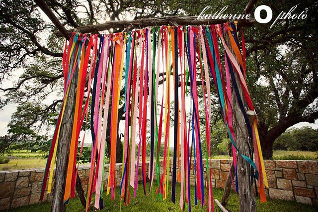 Back drop behind photo booth.  Ribbons, Pom Poms & Papel Picado – Roxana & John's Amazing Fiesta Wedding