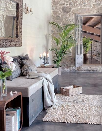concrete floors, white walls, and an accent stone wall
