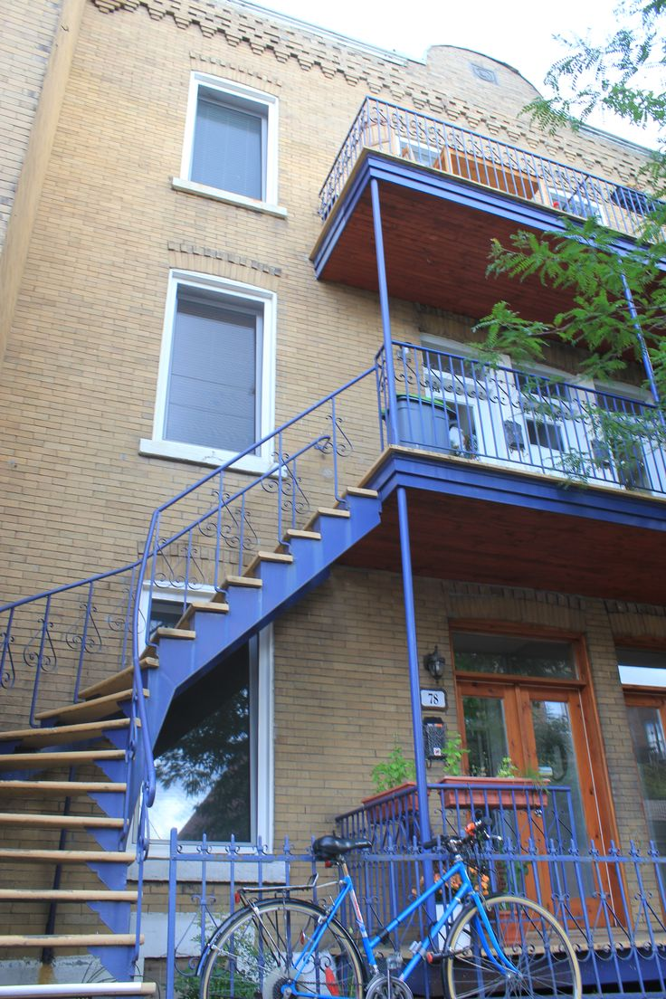 Montreal residential streets are lined triplexes with outside stairwells made of wrought iron railings.