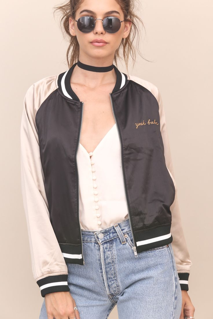 Embroidered satin bomber jacket. Side pockets. Front zipper closure. Fully lined. Style #: 6IT0103C Material: Polyester/Spandex Color: Black/Champagne Model is wearing a small