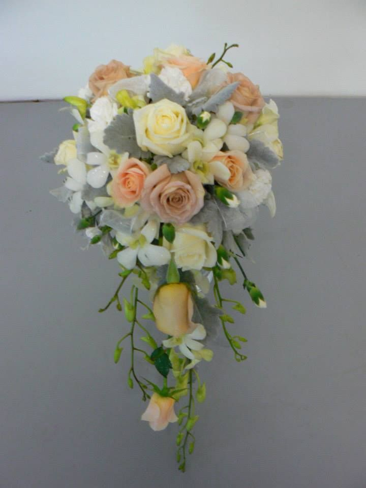 Antique teardrop style bouquet with coffee, cream & apricot roses mixed with white Dendrobium orchids & spray carnations, finished off with a soft dusty miller foliage
