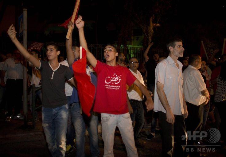イスラエル北部のハイファ(Haifa)で、同国軍のガザ地区(Gaza Strip)への攻撃に抗議するイスラエルのアラブ人と左派活動家ら(2014年7月19日撮影)。(c)AFP/AHMAD GHARABLI ▼20Jul2014AFP|ガザ地区の戦闘激化、双方の犠牲者347人に http://www.afpbb.com/articles/-/3021014