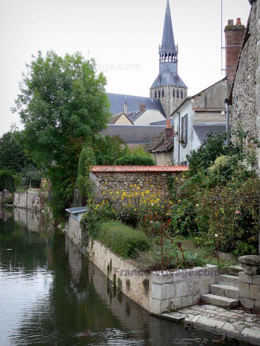Bonneval : Église Notre-Dame de style gothique et sa flèche, jardin fleuri et maisons du village au bord de la rivière Loir (fossé en eau) ; dans la Beauce