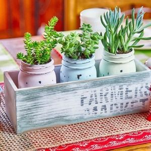 This distressed mason jar centerpiece is sure to bring a pop of color to your spring decor with its lively succulents and homemade chalky paint! 🌼 It's hard to believe I started it out with nothing more than a few bottles of acrylics, some jars, and a plain wooden box (all courtesy of @orientaltrading!) 😉  Check out the tutorial #ontheblog 🔹clickable link in profile🔹#orientaltrading #contest #sp