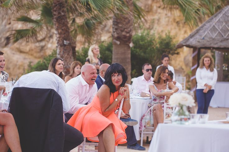 One of a set of images taken at this destination wedding of Maya and Phill, Ibiza. The guests laugh during the speeches at The Amante Beach Club. Wedding Photography by Matt Porteous & Max Burnett