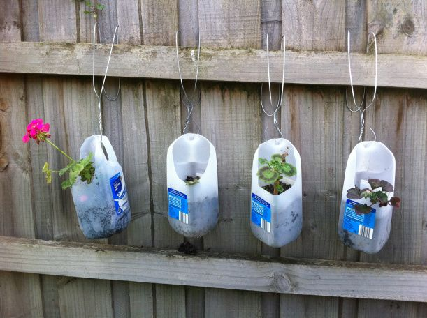 Milk jug planters on a fence using wire clothes hangers