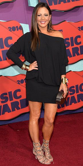 Country's Hottest Shine at the CMT Music Awards | SARA EVANS | The brunette beauty makes her off-the-shoulder Ramy Brook mini pop with a gold fish-shaped clutch by Ashlyn'd paired with Charles Albert statement jewelry and animal-print lace-up heels.
