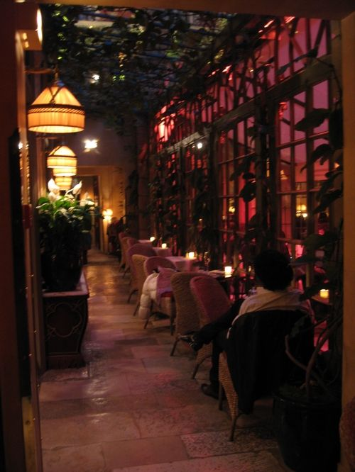 "Restaurant ""Chez Costes"" in Paris this is a lovely colorful and romantic setting with all the tables at the window to witness the lovely view with the sun setting down and all the low light setting"