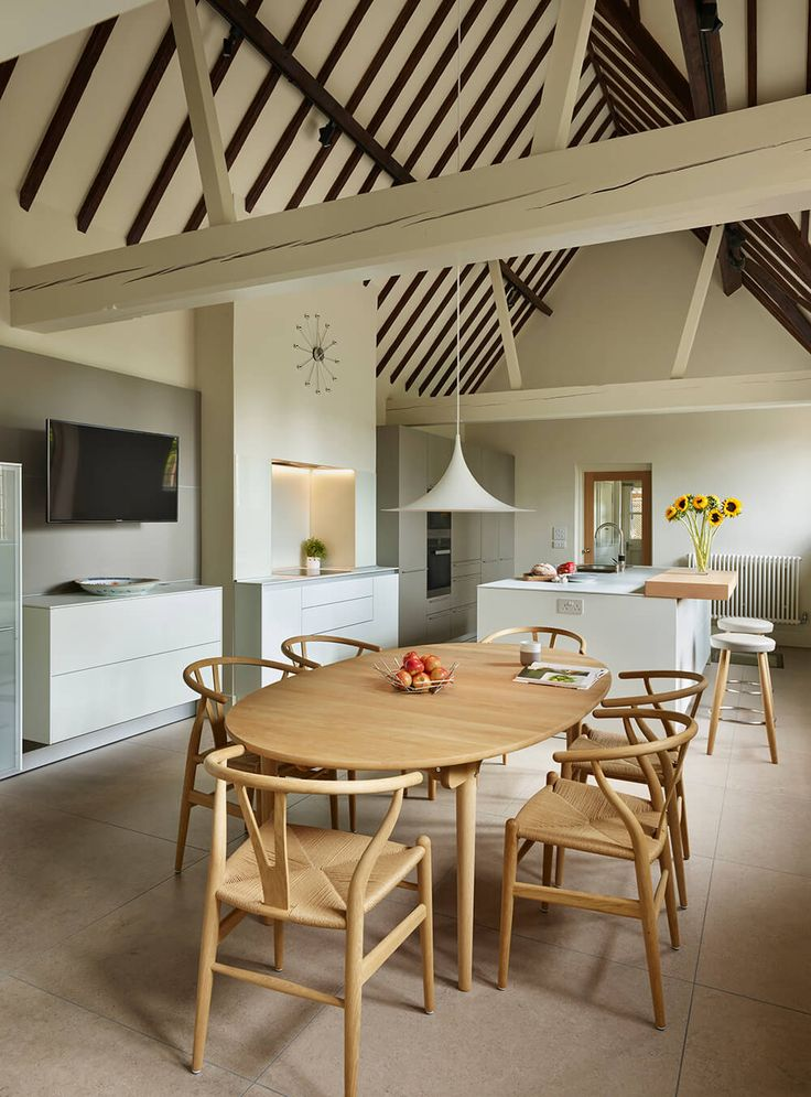 Carl Hansen CH24 Oak Soap 'Wishbone' chairs surround the CH338 dining table. The bulthaup b3 wall system securely holds the 'floating' sideboard and flatscreen TV in place.