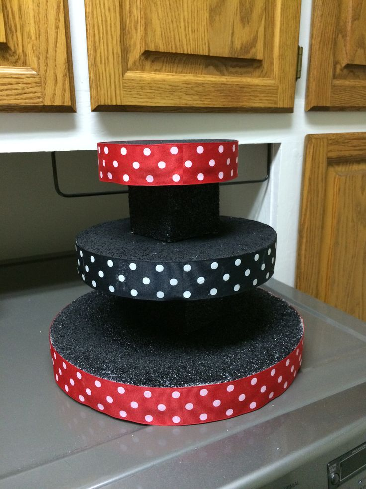 Mickey Mouse Cake pop stand, made my own for about $15. 3 different sizes of styrofoam discs and two square blocks to hold the first two. Painted each one with acrylic black paint. Hot glued the blocks to the discs. Double sided tape the ribbon to the sides. Super easy and inexpensive. Bought everything at Joann's with coupons!