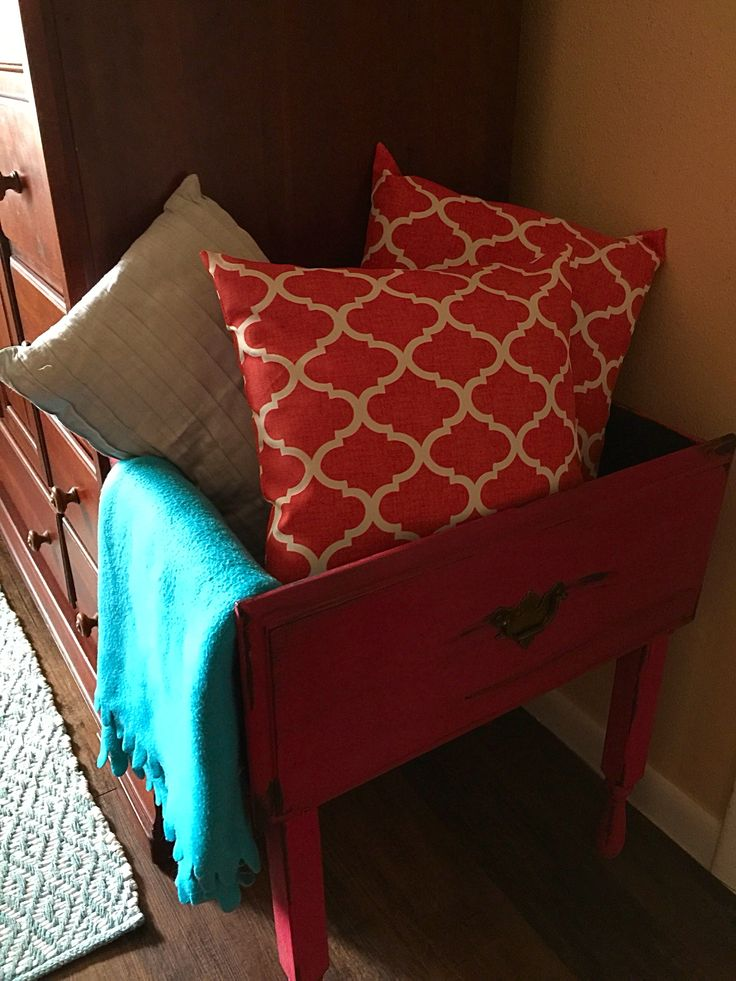 Accent pillows and throw  displayed in an antique drawer that was converted into a storage table