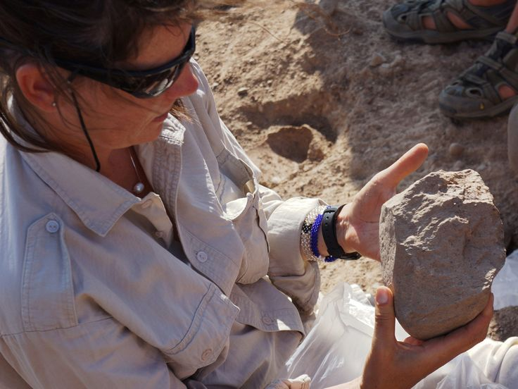 In this photo made available in May 2015 by the Mission Prehistorique au Kenya - West Turkana Archaeological Project, Sonia Harmand holds a stone tool found in the West Turkana area of Kenya.