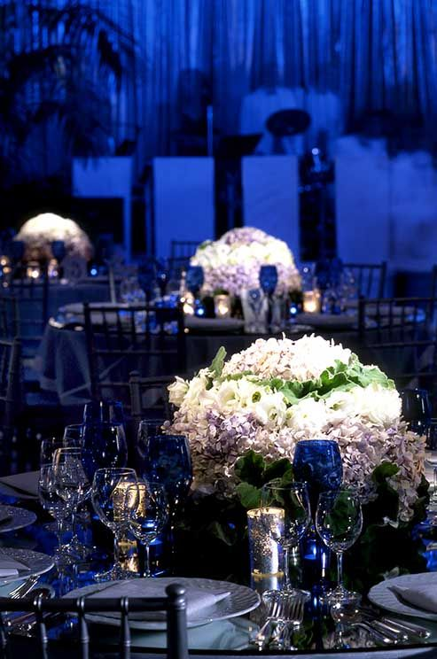 Blue lighting is accented with the soft glow of mercury glass candles and arrangements of mixed white blooms.