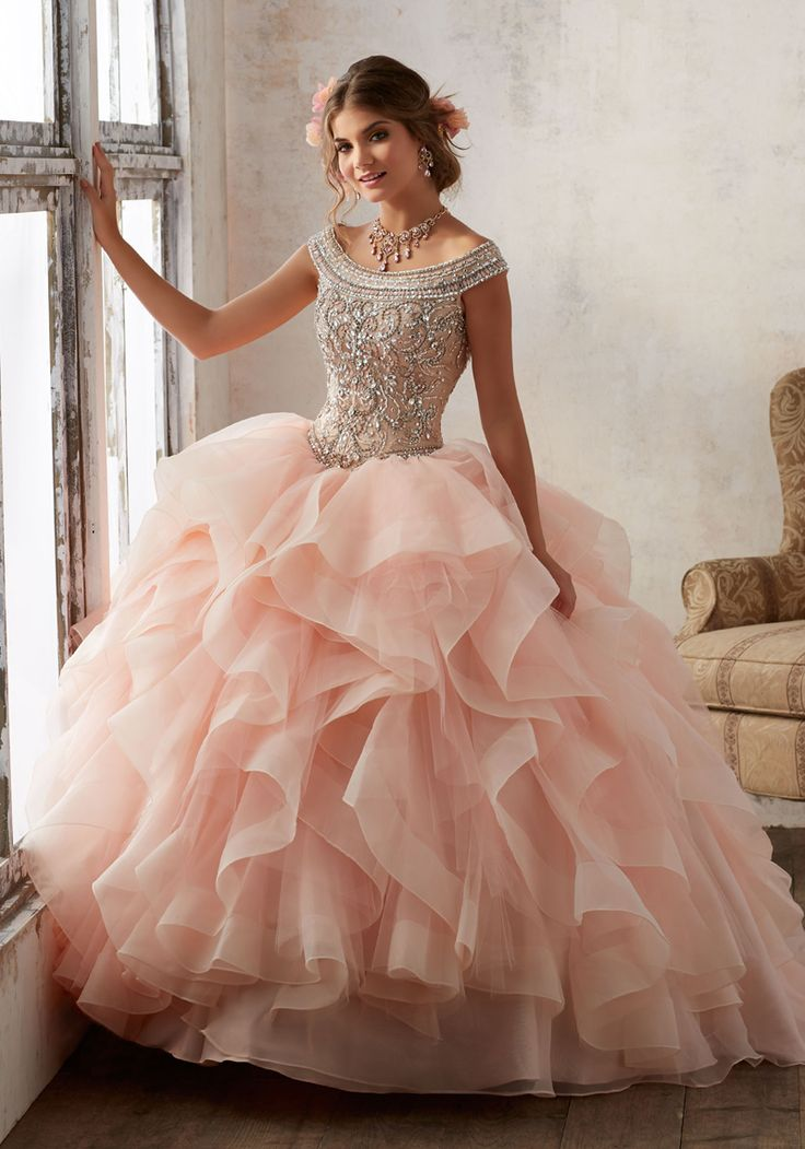 This Mori Lee 89138 off-the-shoulder quinceanera dress with a ball gown silhouette has a beaded bodice with a cutout framed above the lace-up back. Horsehair trim accents the flounced organza skirt as it cascades from the basque waistline. A matching bolero complements this gown.