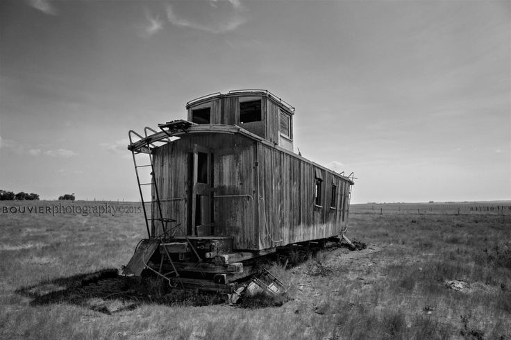 Lonely Old Caboose. caboose; abaonded; prairies; Saskatchewan; old; falling in; weathered; decay; rural decay; peeling paint; broken windows; grassy field; southern Saskatchewan; RM of Shamrock; old train; black and white